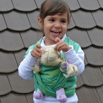 Lachendes Mädchen, die Ihre Puppe in einem grünen Puppentragtuch von DIDYMOS umgebunden hat.