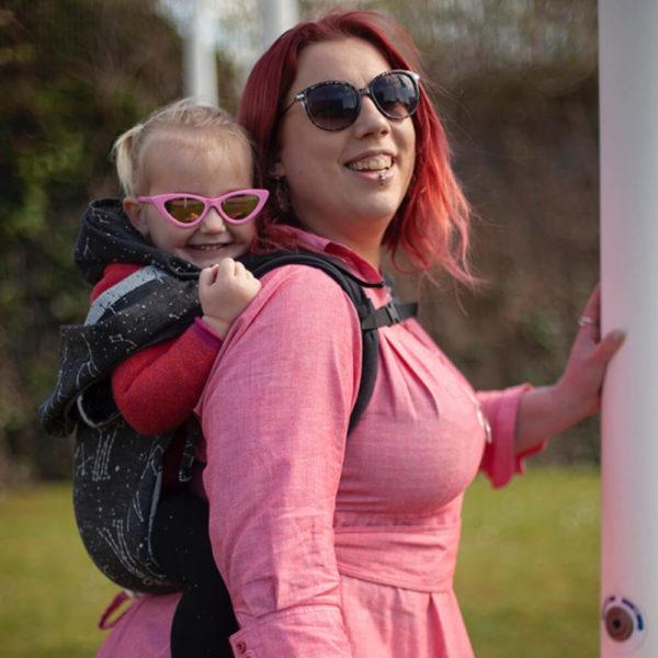 Lifestyle Bild Mutter und Kind mit Sonnenbrillen zeigen wie man Didymos_DidyGo_the-joy-of-baby-wearing_68263_2b traegt