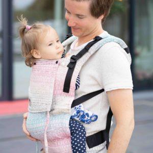 Lifestyle Bild Vater laechelt Kind in Babytrage LIMAS-Flex Aurora 01-klein an
