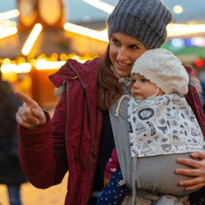 Lifestyle Bild Mama zeigt Kind in LIMAS Babytrage Abenteuer den Weihnachtsmarkt