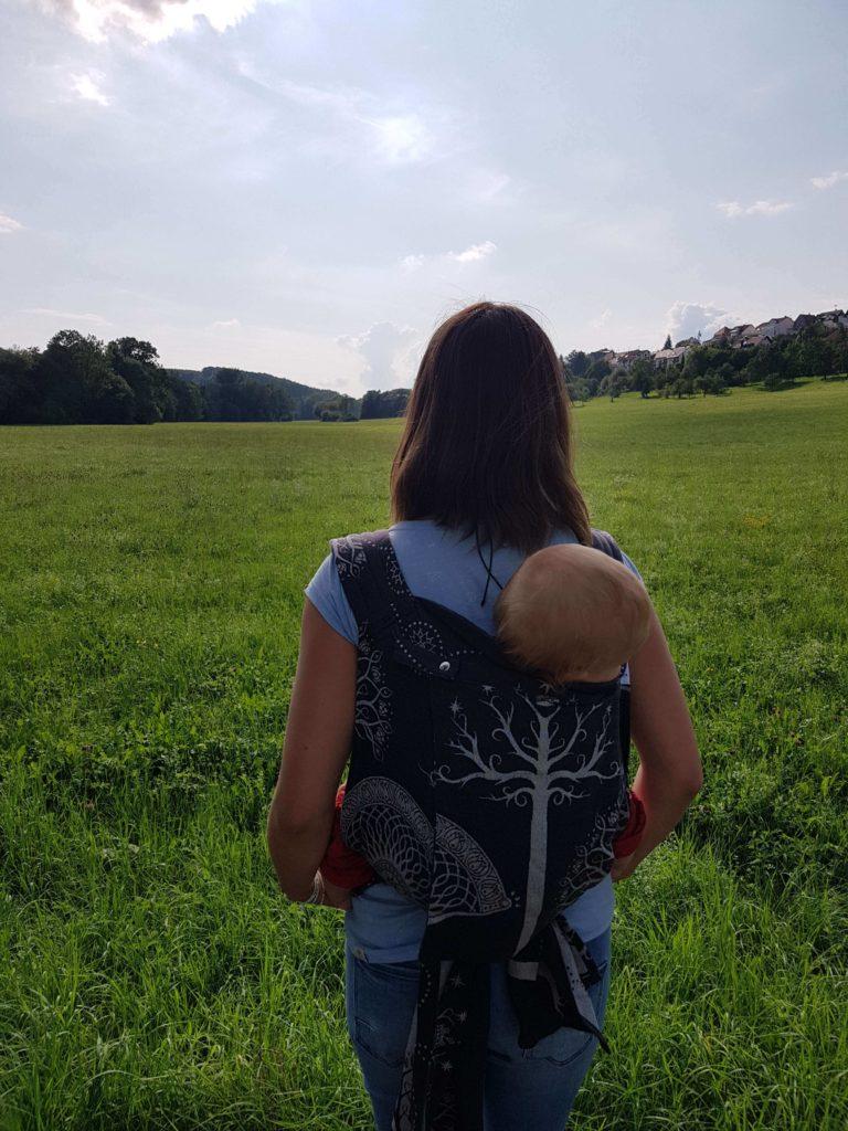 Lifestyle Bild Mutter auf Wiese Baby in Erfahrungen Oscha Cairis Babytrage 20190803_173834