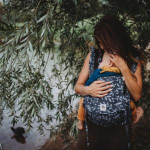 Lifestyle Bild Mutter und Kind in LIMAS_Babytrage Flex Flora Midnight Blue 03 stehen vor einer Weide am Seeufer