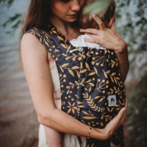 Lifestyle Bild Mutter haelt Kind in LIMAS Babytrage Flora Honey Moon_02 schuetzend an Po und Nacken