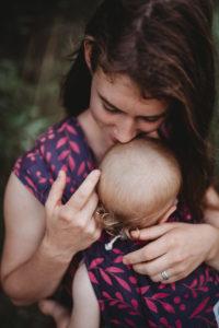 Lifestyle Bild Mutter kuesst Kind in LIMAS_Babytrage Flora Poppy Pink 03