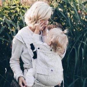 Lifestyle Bild Kleinkind in LIMAS Plus Babytrage mit Leinen Valerien drückt Mutter die Backen