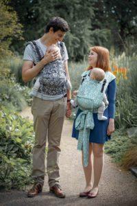 Lifestyle Bild Mann und Frau lächeln sich mit Babies in LIMAS Plus Babytrage Flora Magic Mint 03 an