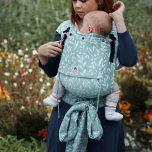 Lifestyle Bild Mutter und Baby in LIMAS Plus Babytrage Flora Magic Mint Ganzkörperansicht auf bunter Blumenwiese