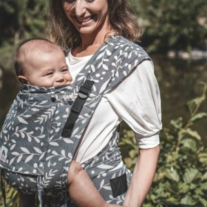 Lifestyle Bild Mutter lächelt Baby in LIMAS_Babytrage Plus Flora Cool Grey-3 an