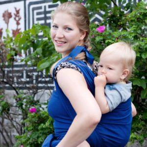 Lifestyle Bild Mutter traegt Kleinkind auf dem Ruecken mit Storchenwiege-Tragetuch-Leo_marine