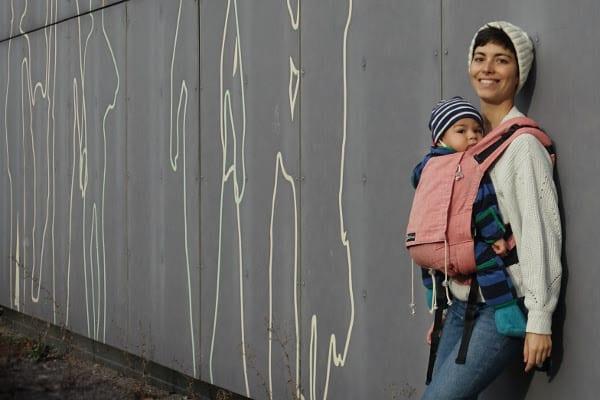 Frau mit rosaner Didymos babytrage (didysnap) lehnt an der Wand
